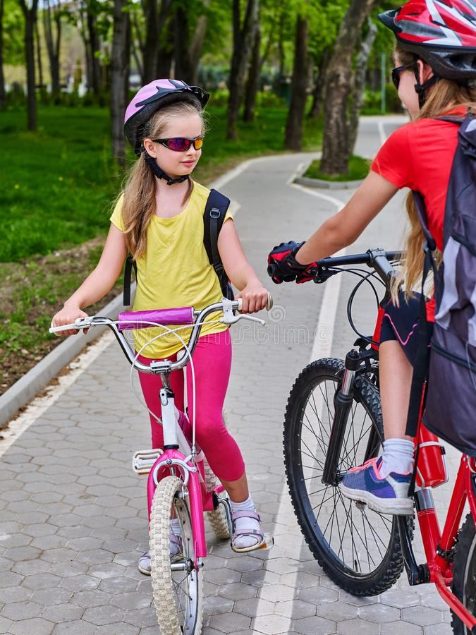 Girls children cycling on spring yellow bike lane. Bikes bicyclist girl. Girls wearing bicycle helmet and glass with rucksack ciclyng bicycle. Walking in spring stock photography