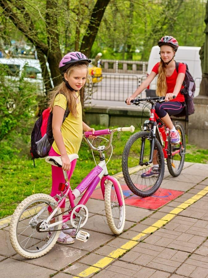 Girls children cycling on yellow bike lane. Girls on bicycle. Bikes bicyclist girl. Girls wearing bicycle helmet with rucksack ciclyng bicycle. Girls children royalty free stock images