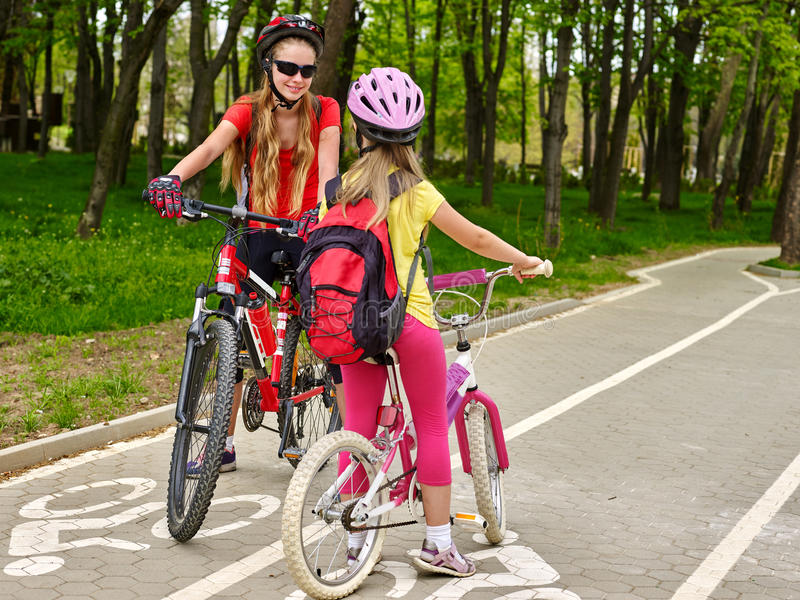Girls children cycling on yellow bike lane. Bicycle girl wearing bicycle helmet and glass with rucksack ciclyng bicycle. Girls children cycling meet on white stock image