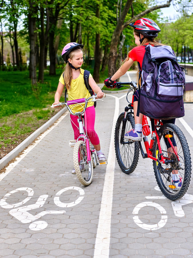 Girls children cycling on yellow bike lane. Bicycle girls wearing bicycle helmet and glass with rucksack ride on bicycle. Girls children cycling meet on white stock images