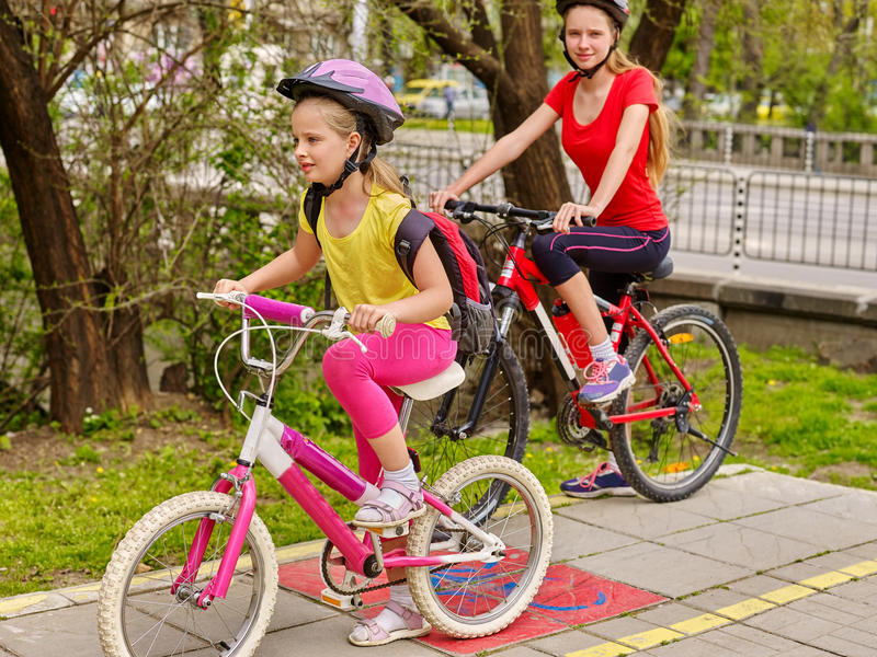 Girls children cycling on yellow bike lane. Bikes bicyclist girl. Two sisters girls wearing bicycle helmet with rucksack ciclyng bicycle. Girls cycling on stock photos