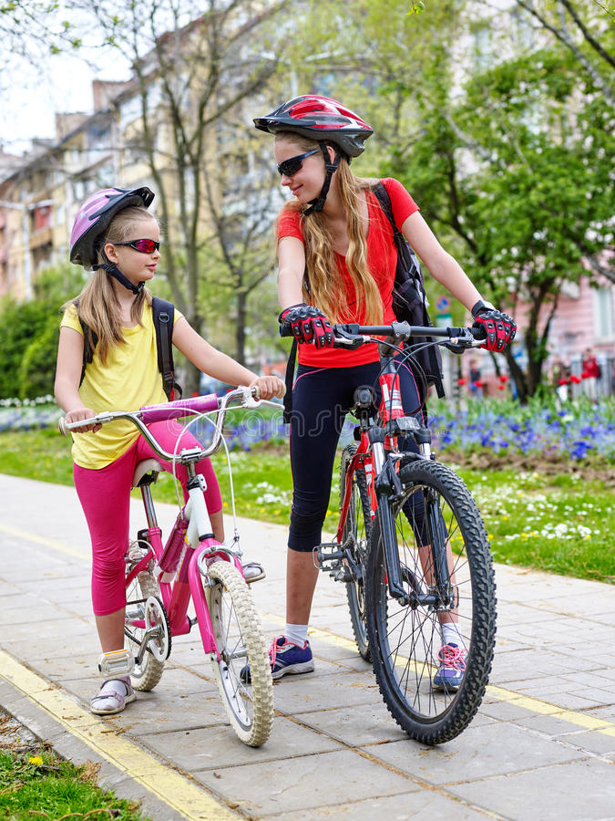 Girls children cycling on yellow bike lane. Bikes bicyclist girl. Girls wearing bicycle helmet and glass with rucksack ciclyng bicycle. Girls children cycling royalty free stock photography