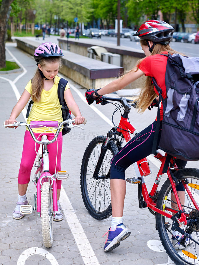 Girls children cycling on yellow bike lane. Bikes bicyclist girl. Girls wearing bicycle helmet and glass with rucksack ciclyng bicycle. Girls children cycling stock photo