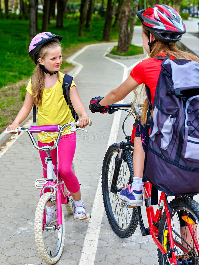 Girls children cycling on yellow bike lane. Bikes bicyclist girl. Girls wearing bicycle helmet and glass with rucksack ciclyng bicycle. Girls children cycling royalty free stock photos