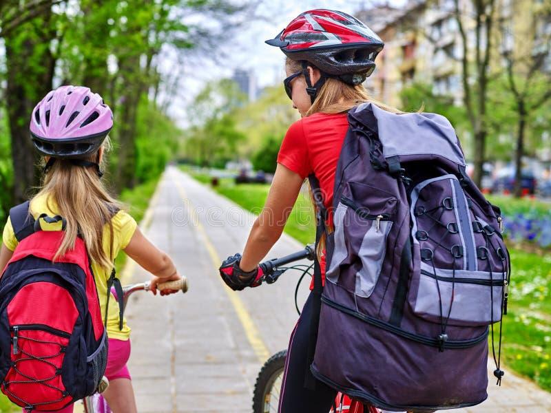 Girls children cycling on yellow bike lane. Bikes bicyclist girls wearing bicycle helmet with rucksack ciclyng bicycle. Girls children cycling on yellow bike royalty free stock photography
