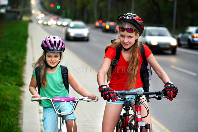 Girls children cycling on yellow bike lane. Cars are road. Bikes bicyclist girl. Girls wearing bicycle helmet and glasses with rucksack ciclyng bicycle. Girls stock photography