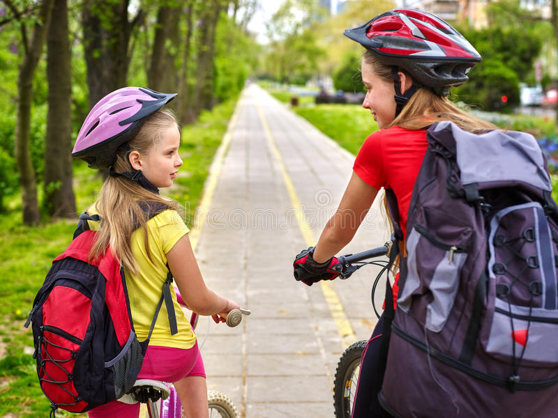Girls children cycling on yellow bike lane and talk. Bikes bicyclist girl. Girls wearing bicycle helmet and glass with rucksack ciclyng bicycle. Girls children stock photos