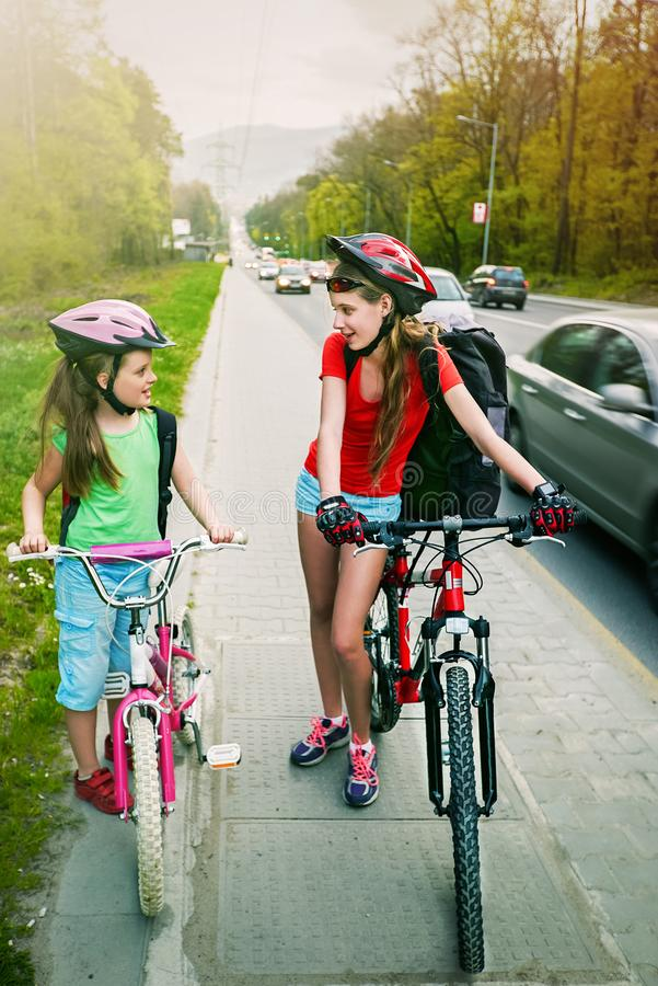 Girls children cycling on yellow bike lane. There are cars on road. Bikes bicycle girl wearing bicycle helmet and glass with rucksack ciclyng. Children cycling royalty free stock photo