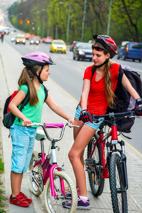 Girls children cycling on yellow bike lane. There are cars on road. Bikes bicyclist girl wearing bicycle helmet and glass with rucksack ciclyng . Children royalty free stock photo