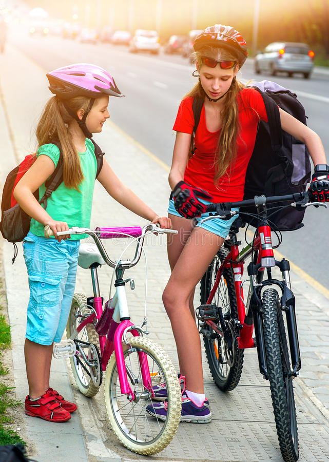 Girls children cycling on yellow bike lane. There are cars on road. Bikes bicyclist girl wearing bicycle helmet and glass with rucksack ciclyng . Children royalty free stock images