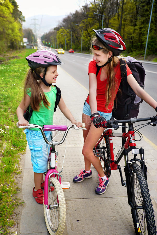 Girls children cycling on yellow bike lane. There are cars on road. Bikes bicyclist girl wearing bicycle helmet and glass with rucksack ciclyng. Cycling on bike stock image