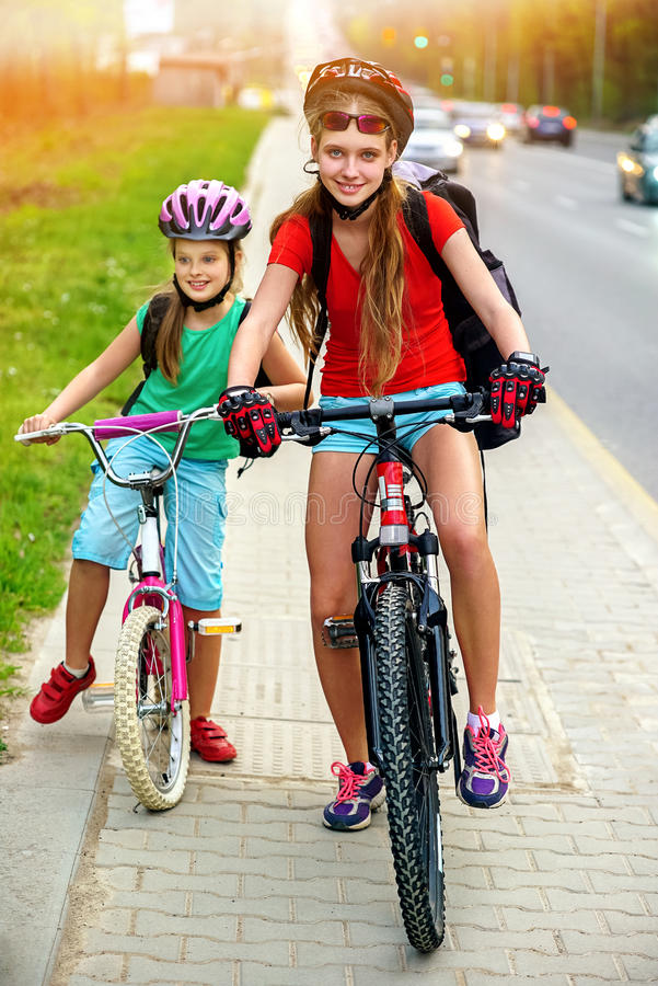 Girls children cycling on yellow bike lane. There are cars on road. Bikes bicyclist girl. Girls wearing bicycle helmet and glass with rucksack ciclyng bicycle royalty free stock photos
