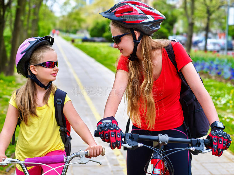 Girls children cycling on yellow bike lane. Girls wearing bicycle helmet and glass with rucksack ciclyng bicycle. Girls children cycling on yellow bike lane royalty free stock images