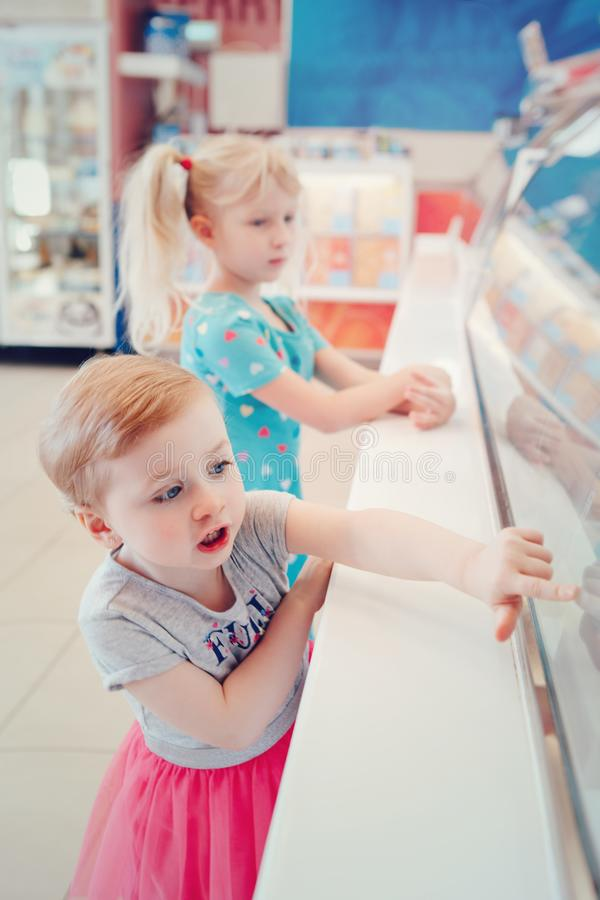 Girls children sisters friends looking at ice cream shop window royalty free stock photography