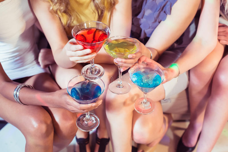 Girls with cocktails toasting. In a club royalty free stock photos