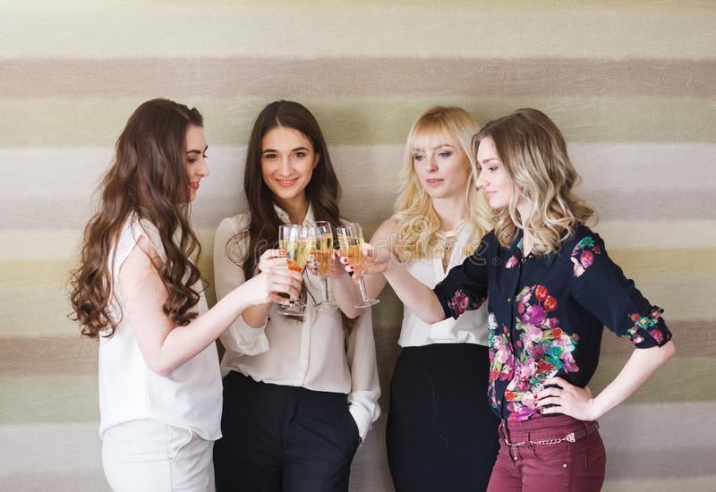 Girls congratulating friend on her birthday with glasses of champagne in hand. royalty free stock images