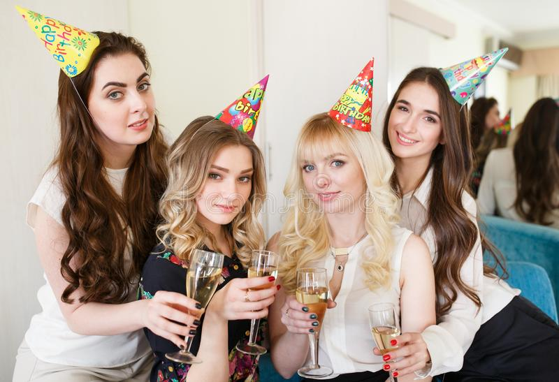 Girls congratulating friend on her birthday with glasses of champagne in hand. stock images