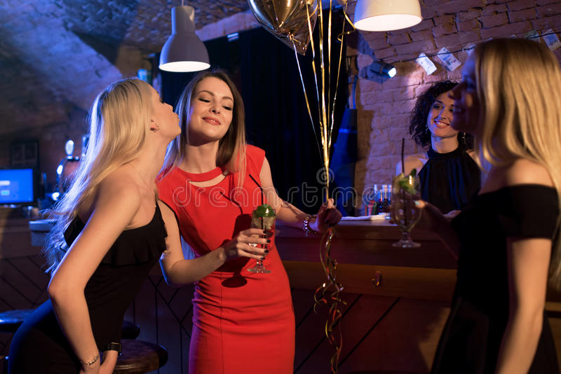 Girls congratulating their friend with her birthday while celebrating the event at night club stock photo