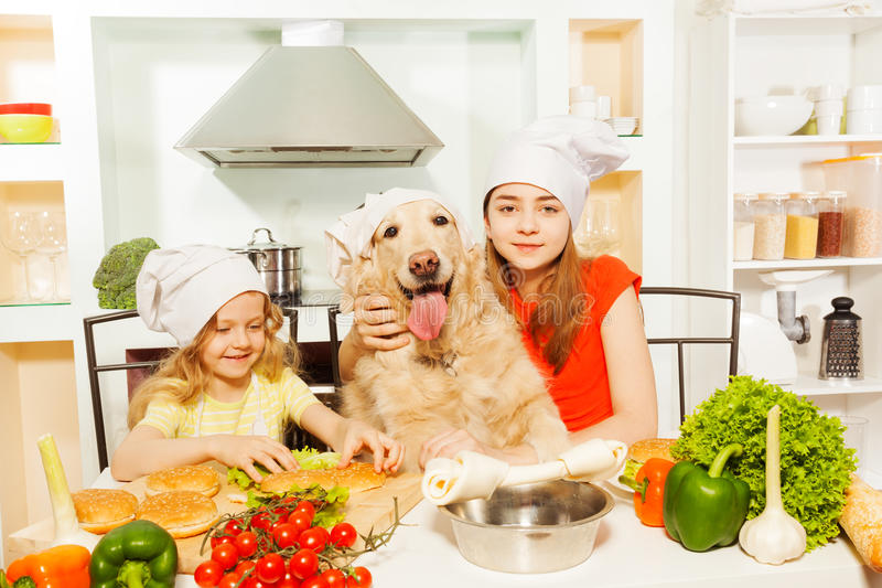 Girls in cook's hats making food with their pet stock photography