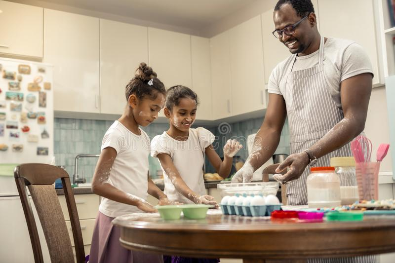 Two funny girls cooking pie with their loving helpful father. Girls cooking pie. Two funny excited girls cooking pie with their loving helpful father stock image