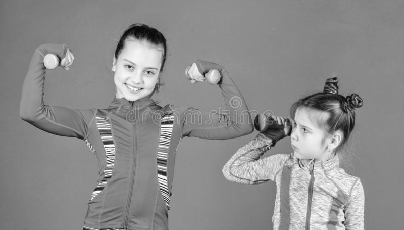 Girls cute kid exercising with dumbbells. Motivation and sport example concept. Toddler repeat exercise after sister. Sport exercises for kids. Healthy stock images
