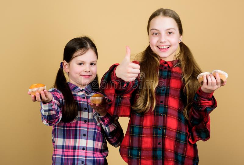 Girls cute kids eating muffins or cupcake. Sweet dessert. Culinary recipe. Tasty snack. Cooking skill. Sisters hold stock photography