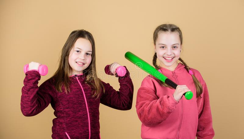 Girls cute kids with sport equipment dumbbells and baseball bat. We love sport. Child might excel in completely. Different sport. Friends ready for training royalty free stock image