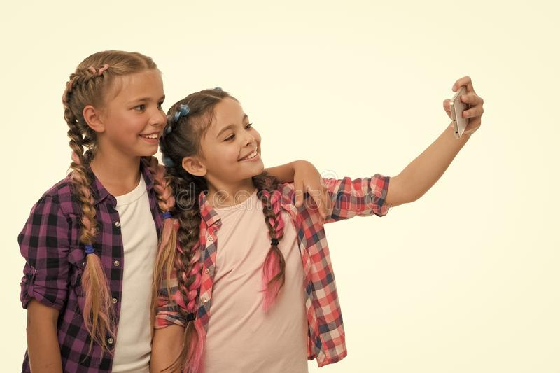 Girls cute small children smiling to phone screen. They like taking selfie for social networks. Problem of young stock images