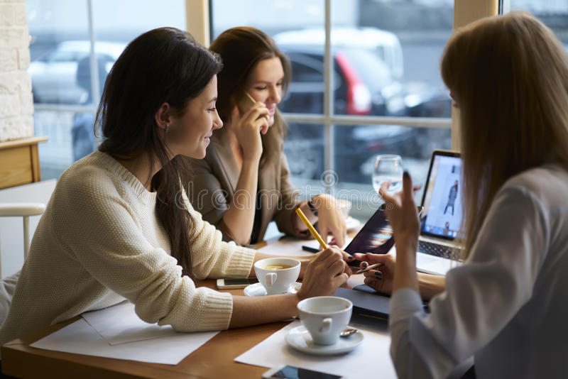 Girls designers clothes working together connected to free wireless internet in coffee shop during break royalty free stock photos