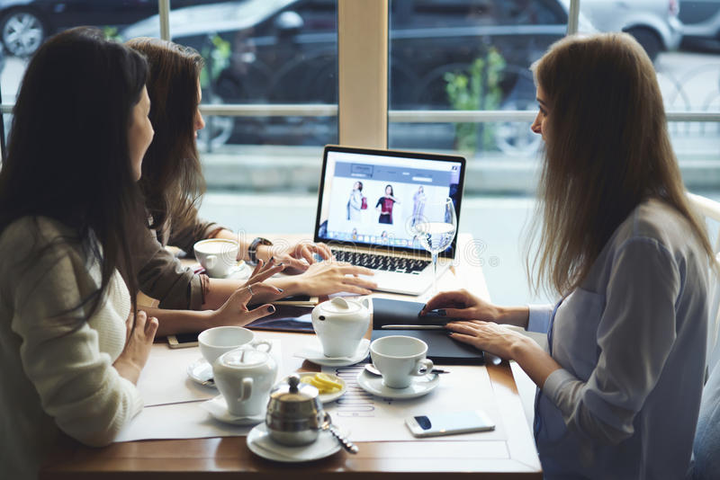 Girls designers clothes working together connected to 5g wireless searching information on travel blogs royalty free stock photos