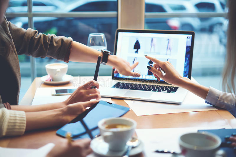 Girls designers clothes working together meeting in cafe with CEO to confirm project before releasing using technologies. Cropped image of skilled female IT royalty free stock photos