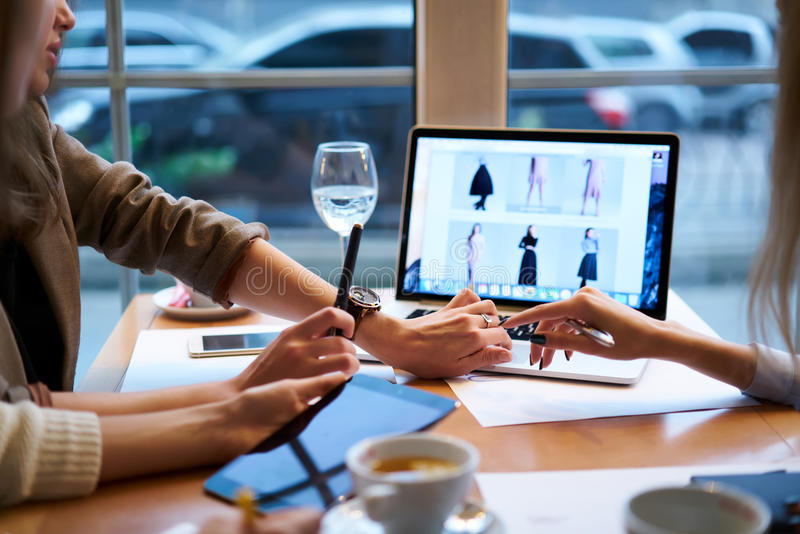 Girls designers clothes working together meeting in cafe with CEO to confirm project before releasing using technologies royalty free stock photography
