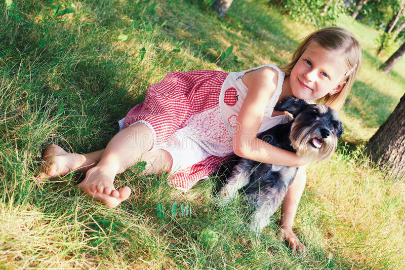 Girls and a dog. Cute girl hugging her dog sitting on the grass royalty free stock photos