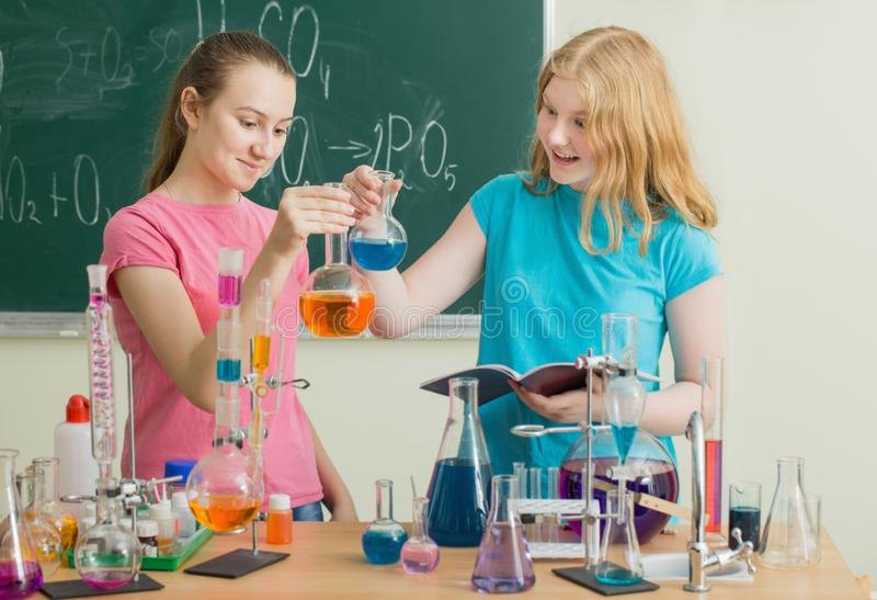 Girls doing chemical experiments. Two girls doing chemical experiments stock photography
