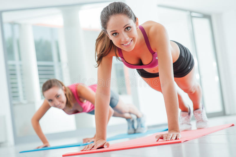 Girls doing push ups at the gym. Young women at the gym doing push ups on a mat, fitness and healthy lifestyle concept royalty free stock photo