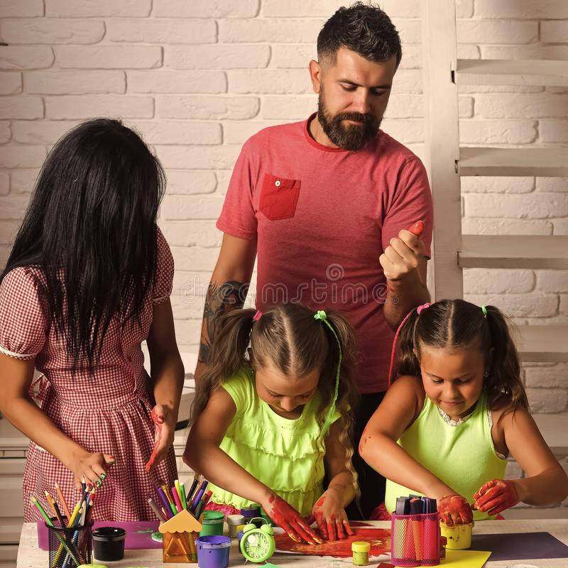 Girls drawing with mother and father. Happy childhood and parenting. Imagination, creativity concept. Finger painting royalty free stock image