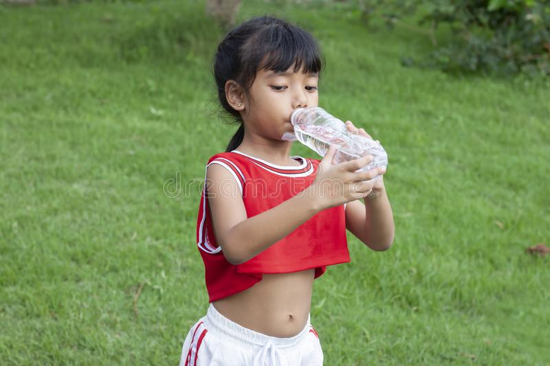 Girls drink water from plastic bottles. To quench thirst. Girls drink water from plastic bottles. To quench thirst after exercise royalty free stock photo