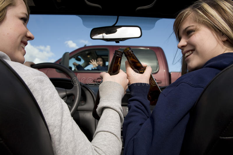 Girls drinking and driving accident. Two teen girls drinking, driving and not paying attention to the truck in front of them that they are about to hit royalty free stock photo