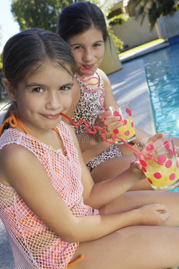 Girls Drinking Juice By Pool's Edge royalty free stock photo