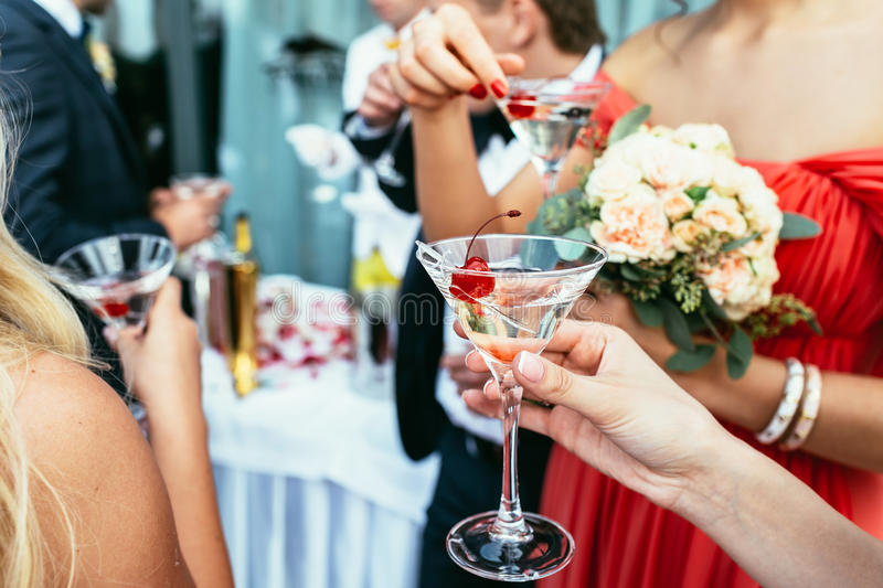 Girls Drinking martini cocktails with red cherry on the wedding stock photo