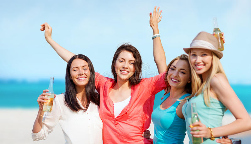Girls with drinks on the beach royalty free stock images