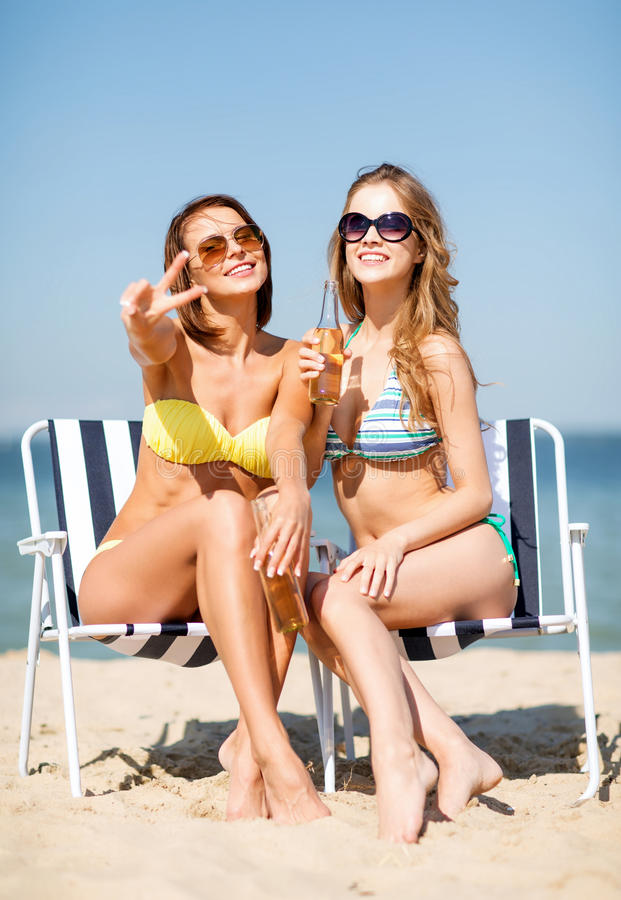Girls with drinks on the beach chairs