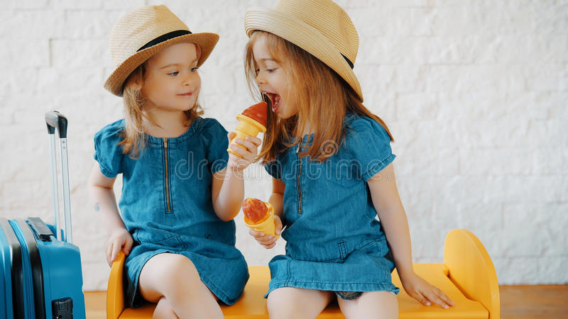Girls eat ice cream at home while waiting for vacation stock photography