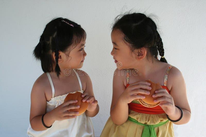 Girls eating burgers royalty free stock image