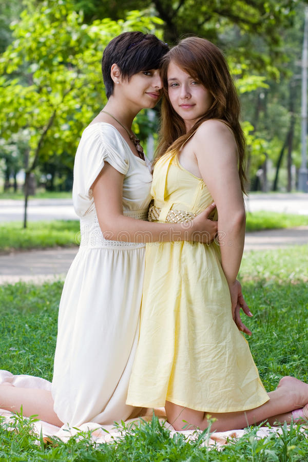 Girls embracing on the coverlet outdoors royalty free stock image
