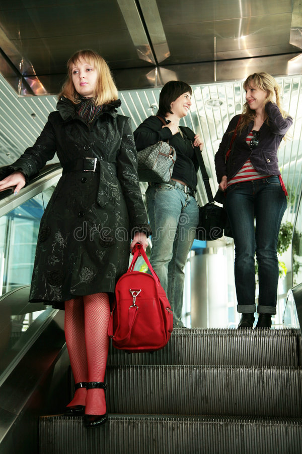 Girls on the escalator at the airport royalty free stock photography