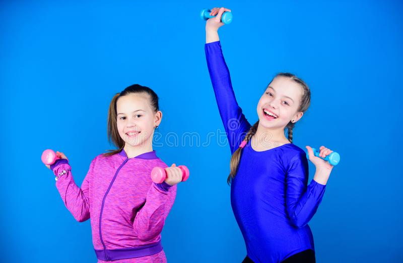 Girls exercising with dumbbells. Beginner dumbbells exercises. Children hold dumbbells blue background. Sport for teens. Easy exercises with dumbbell. Sporty stock photography
