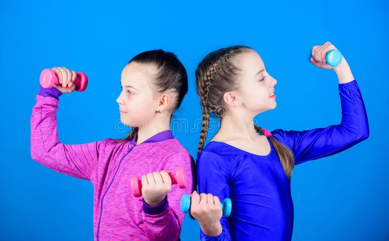 Girls exercising with dumbbells. On way to stronger body. Beginner dumbbells exercises. Sporty upbringing. Children hold. Dumbbells blue background. Sport for royalty free stock photo