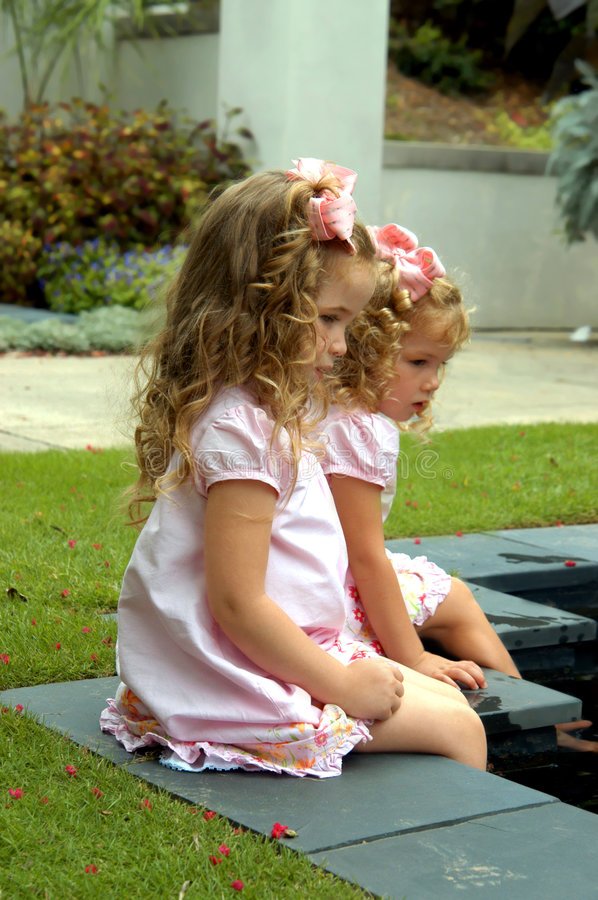 Girls explore park. Two little girls stick their feet into a waterfountain in a park. Both are dressed identically royalty free stock photography