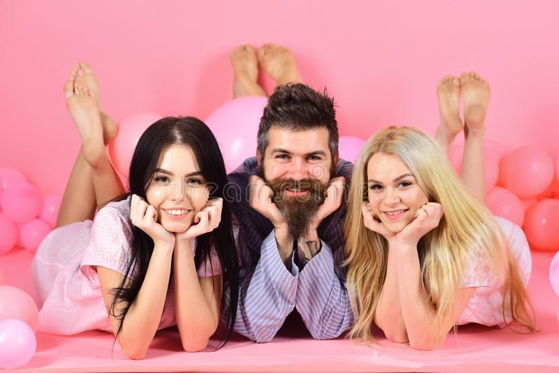 Girls fall in love with bearded macho, pink background. Alpha male concept. Man with beard and mustache attracts blonde. And brunette girls. Threesome on stock photos